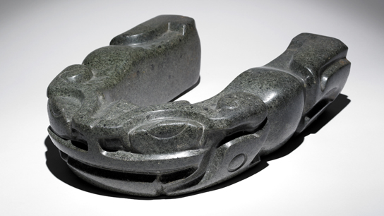 Greenstone yoke mould with relief carving in the form of a toad. Used to shape the protective leather belts worn by players of the Mesoamerican ballgame. From Veracruz, Mexico, AD 300-1200 (AOA Am,St.398)